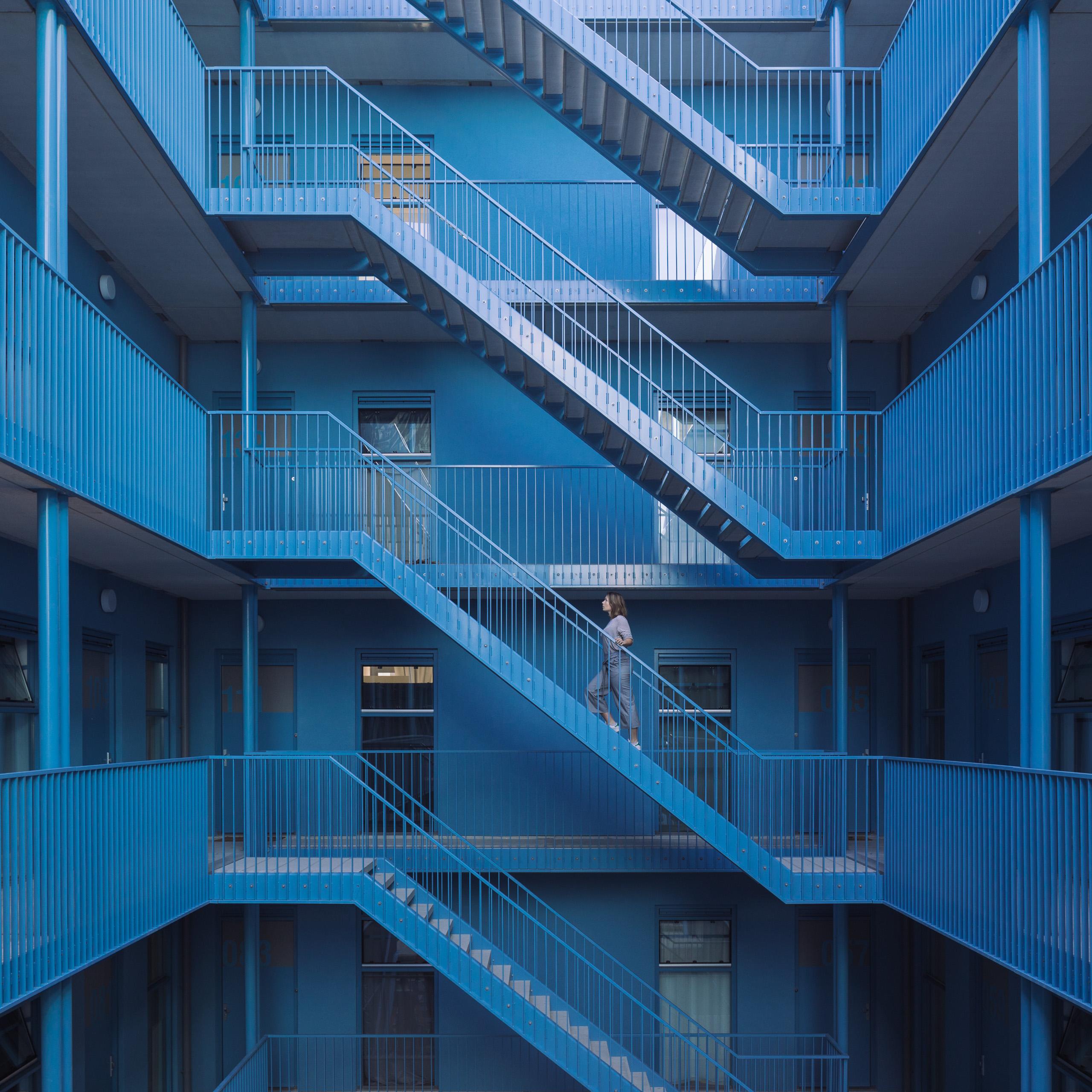 Eindhoven Strijp-S fabrieksarchitectuur lofts loftwonen baksteenarchitectuur vakmanschap blauw binnenruimte trappen woongebouw blok 61 fabrieksgebouw rode baksteen binnenhof blauw binnenhof blauw atrium hemelsblauw Cubies